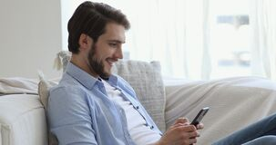 Smiling man enjoying communicating in social network on phone.