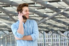 Smiling man enjoying conversation on cell phone Stock Photo