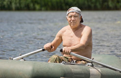 Smiling man enjoying a row in a rubber dinghy Stock Photo