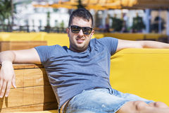 Smiling  man  enjoying the summer vacation lying on a sunbed in a sea bar. Handsome man  enjoying the summer laying on sunbed , sunbathing and relaxing Royalty Free Stock Photography