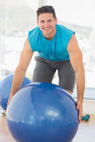 Smiling man exercising with fitness ball at gym Stock Photos