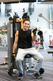 Smiling man exercising on gym machine Royalty Free Stock Photography