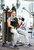Smiling man exercising on gym machine Royalty Free Stock Photo