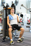 Smiling man exercising on gym machine Stock Photography