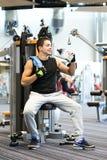Smiling man exercising on gym machine Stock Photos
