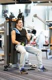 Smiling man exercising on gym machine Stock Photo