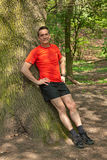 Smiling Man Exercising and Relaxing against a Tree Royalty Free Stock Image