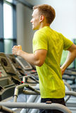 Smiling man exercising on treadmill in gym Royalty Free Stock Photography