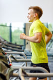 Smiling man exercising on treadmill in gym Royalty Free Stock Images