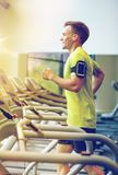 Smiling man exercising on treadmill in gym. Sport, fitness, lifestyle, technology and people concept - smiling man with smartphone and earphones exercising on Stock Photo