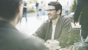 A smiling man in eyeglasses in a cafe outdoors stock photos