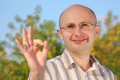 Smiling man in fall park with OK hand gesture Stock Photography