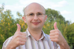 Smiling man in fall park with thumbs up gestures Royalty Free Stock Photo