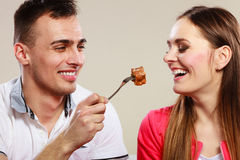 Smiling man feeding happy woman with cake. Stock Photography