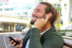 Smiling man with finger to ear listening to music Royalty Free Stock Images