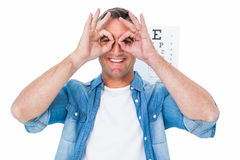 Smiling man with fingers around his eyes Stock Photography