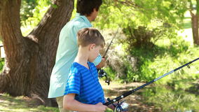 Smiling man fishing with his son Stock Photo