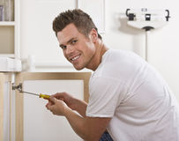 Smiling Man Fixing Cabinet Door Royalty Free Stock Photos