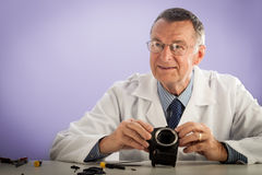 Smiling Man Fixing Camera. An older male wearing a white lab coat and repairing electronic equipments, like a technician or a repair man Stock Photos
