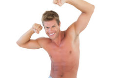 Smiling man flexing muscles Stock Images