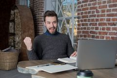 Smiling man freelancer raising hand in yes gesture, celebration victory, looking on laptop computer. stock photos