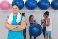 Smiling man with friends in background at fitness studio Royalty Free Stock Images