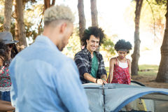 Smiling man with friends setting up tent Royalty Free Stock Photo
