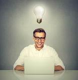 Smiling man in front of computer with light bulb over head Stock Images