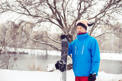 Smiling man in a funny hat with snowboard. Standing in the city park and preparing to ride. Toned image Stock Photo