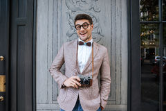 Smiling man in funny round glasses holding vintage photo camera Royalty Free Stock Photo