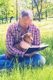 Smiling man with a funny small dog is reading a book. While sitting on a meadow, among green fresh grass. Sunny day in the park Royalty Free Stock Photo