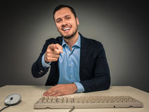 Smiling man is gesturing with hand, pointing finger at camera Royalty Free Stock Image