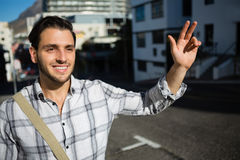 Smiling man gesturing while standing on city street Royalty Free Stock Photos