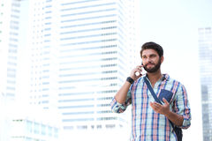 Smiling man gesturing while using cell phone in city Stock Photography