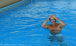 Smiling man getting out of blue swimming pool wate Royalty Free Stock Image
