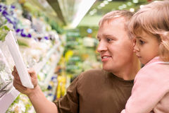Smiling man with girl buy parsley in supermarket Stock Image