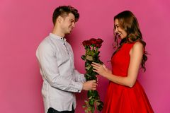 Smiling man gives red roses to his charming girlfriend stock photography