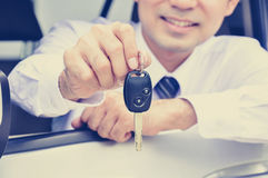 Smiling man giving car key Royalty Free Stock Image