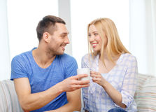 Smiling man giving cup of tea or coffee to wife Royalty Free Stock Image