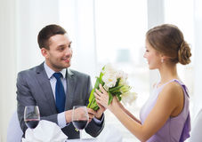 Smiling man giving flower bouquet at restaurant Royalty Free Stock Photography