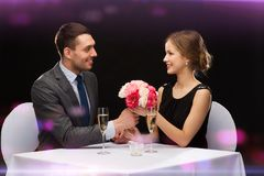 Smiling Man Giving Flower Bouquet To Woman Stock Photo