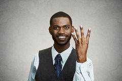 Smiling man giving four times gesture with hand royalty free stock image