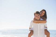 Smiling man giving girlfriend a piggy back looking at camera stock photography