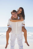 Smiling man giving happy girlfriend a piggy back looking at came Royalty Free Stock Images