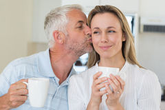 Smiling man giving his partner a kiss on the cheek Stock Image