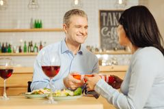 Smiling man giving present to his beloved woman. Happy Birthday. Handsome joyful well-built men smiling and giving a present to his attractive beloved happy Royalty Free Stock Images
