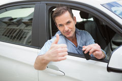 Smiling man giving thumbs up and holding key Royalty Free Stock Image