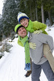 Smiling man giving wife a piggyback ride in snowy woods Royalty Free Stock Photos