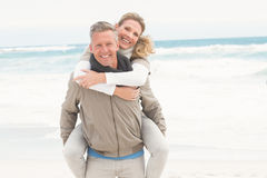 Smiling man giving woman a piggy back Royalty Free Stock Image