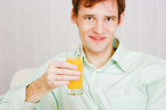 Smiling man with a glass juice Royalty Free Stock Image